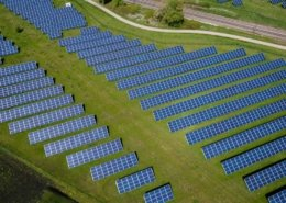 Aerial view of many solar panels in a green field. Photo.